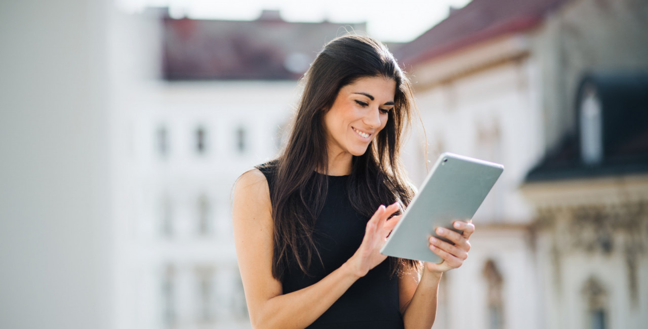 Young businesswoman with tablet standing on a terrace outside an office in city (iStock/ @Halfpoint)