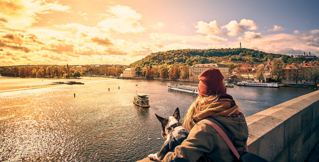 A young woman and her dog take in a view overlooking the Vltava River from Prague's Charles Bridge