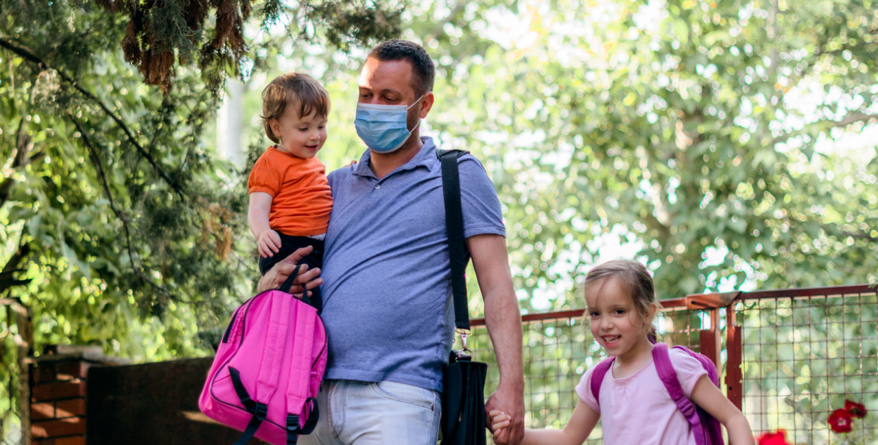 Father wearing a face mask brings his children to school via iStock / StockPlanets