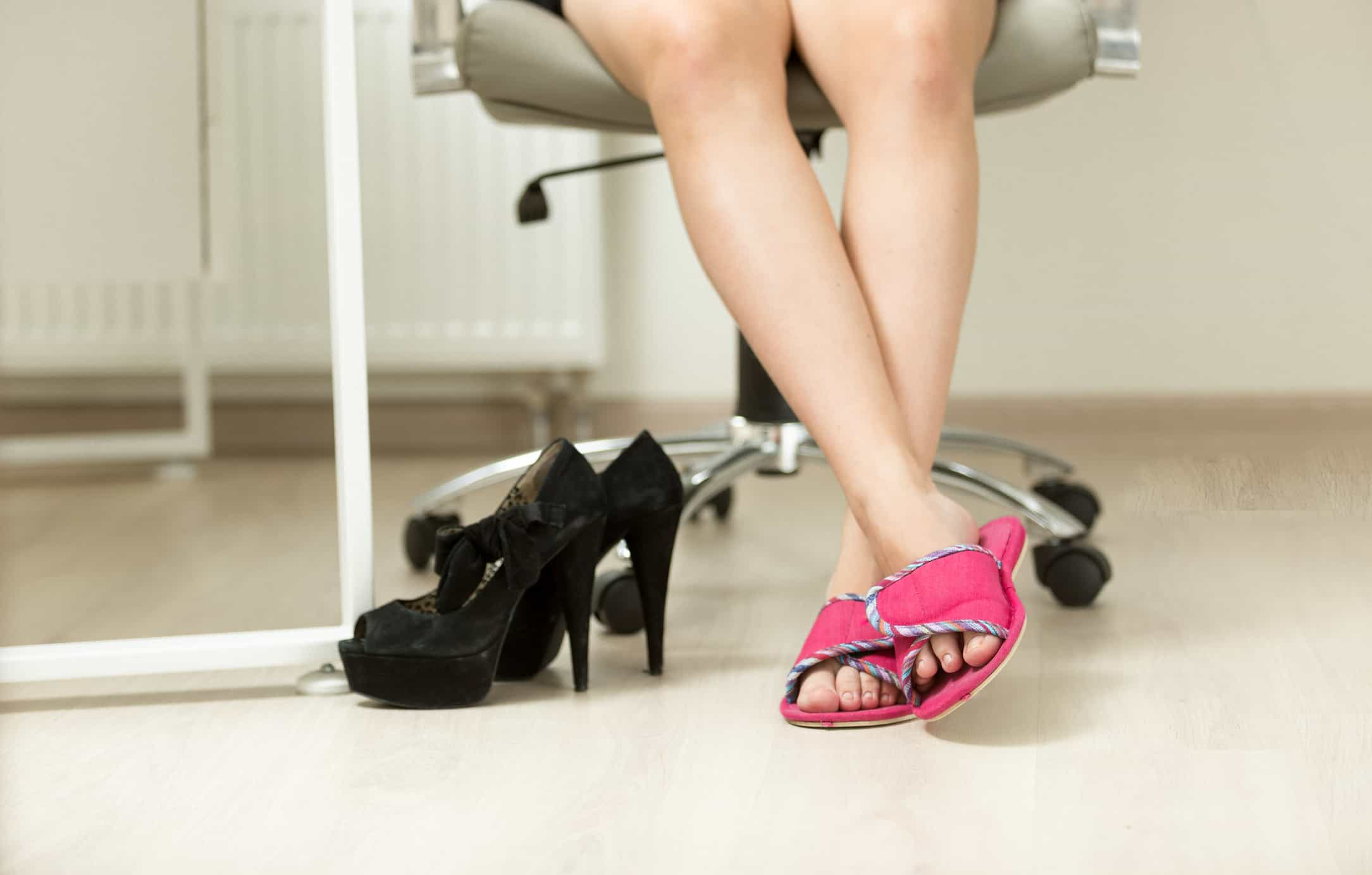 Closeup photo of businesswomen feet in slippers under office table