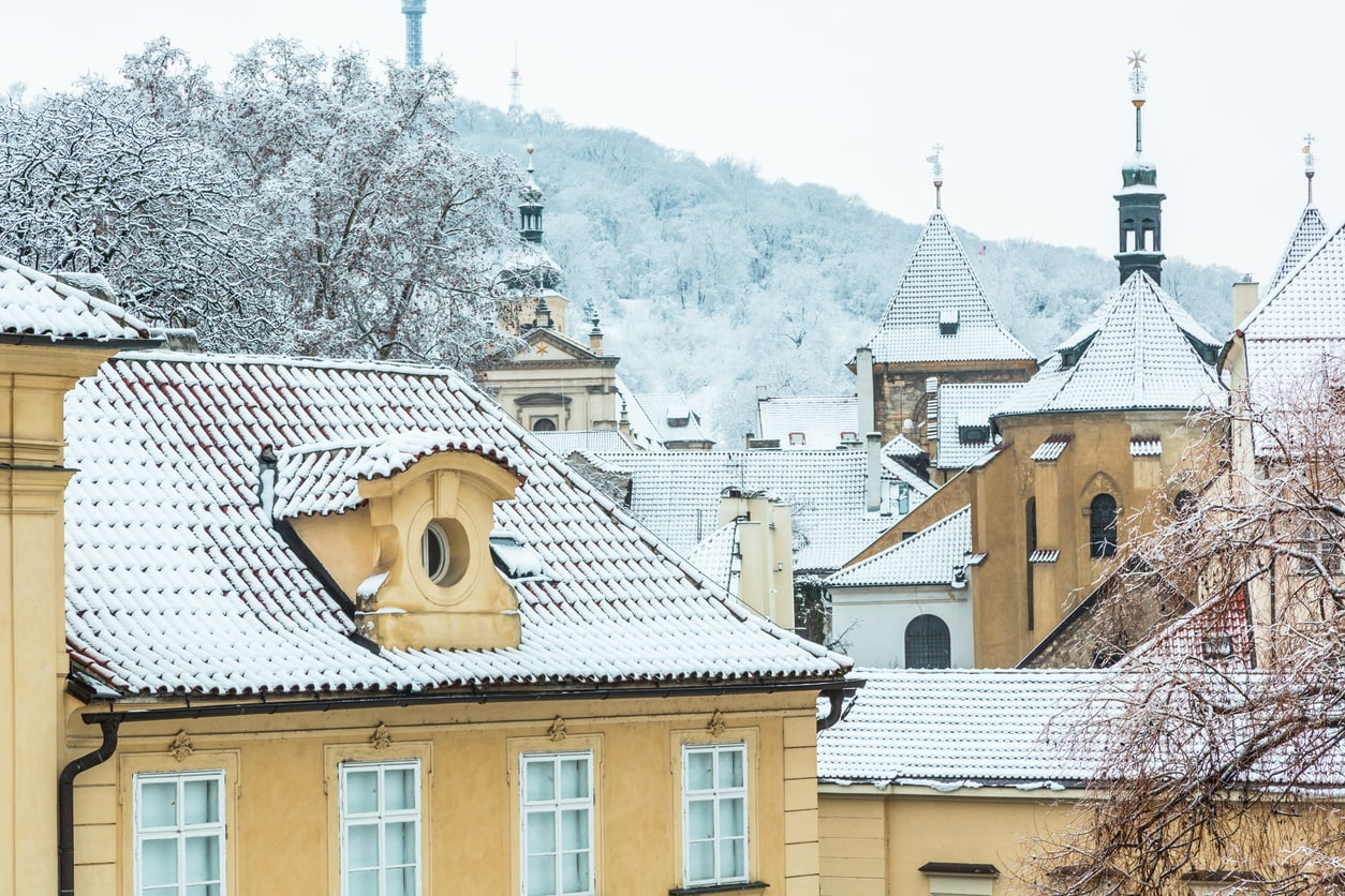 Snow-covered tiled roofs of  Malá Strana in front of the Petřín Hill and Tower.