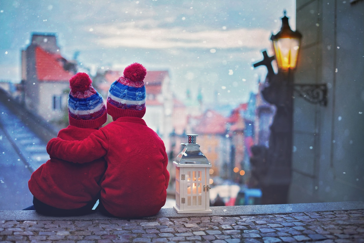 Snow falls in front of two young boys on the streets of Malá Strana.