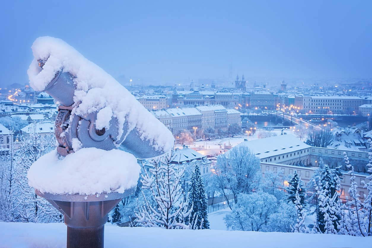 A snow-covered sightseeing Telescope outside Prague Castle overlooking Malá Strana.