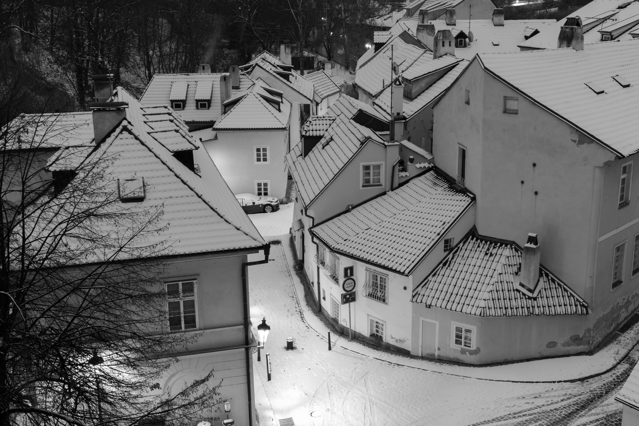 Snow-covered streets and roofs in the romantic Nový Svět district in central Prague, illuminated by vintage street lamps.