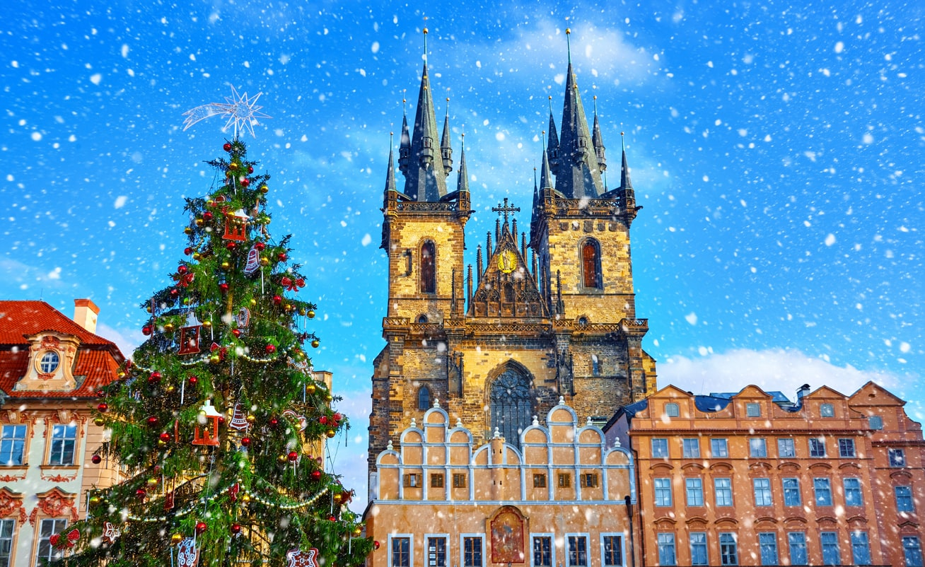 Snow falls over the famed Christmas Market Prague's Old Town Square, Czech Republic in front of Church of Our Lady Before Týn.