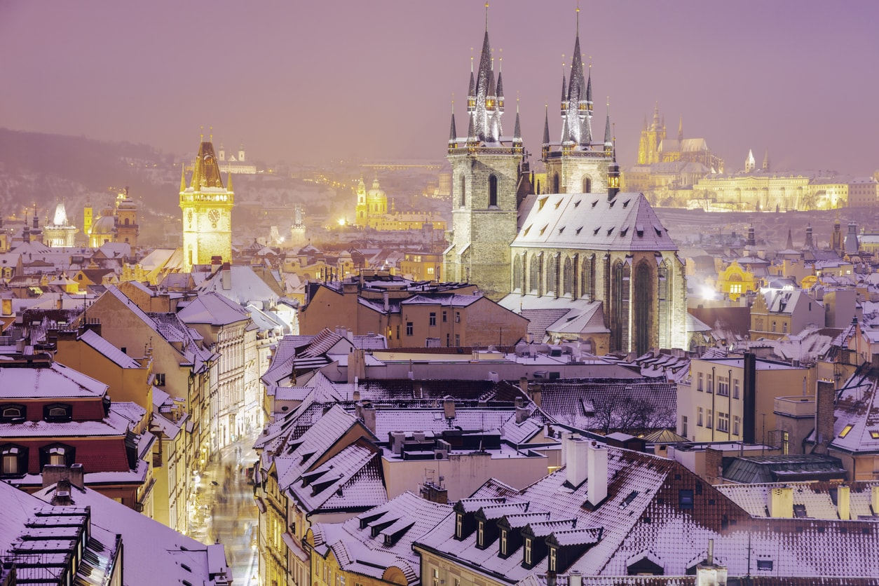 A snow-covered Prague winter cityscape with the Church of Our Lady Before Týn, Old Town Hall Clock Tower, and Prague Castle in the distant background.