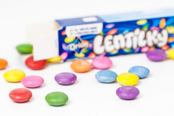 Udine, Italy - December 4, 2012: Lentilky colorful chocolate candies sparse on a white table. The paper box, is visible in the background. The brand is from a Czech company.""