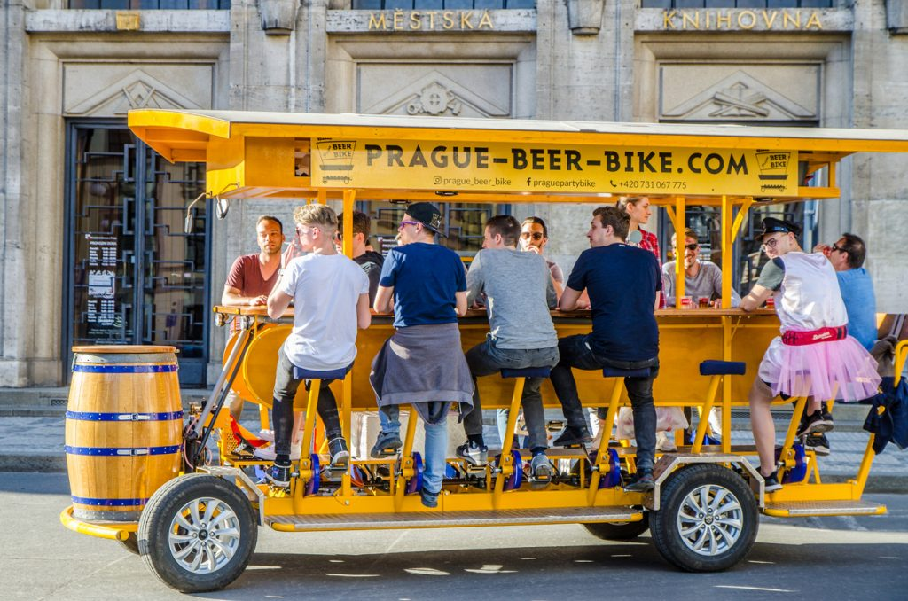 Tourists pedal a beer bike through the center of Prague