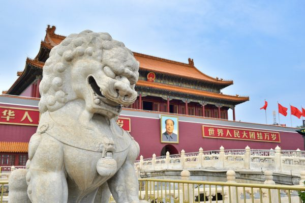 Guardian lion statue and portrait of Mao Zedong at the Gate of Heavenly Peace in Beijing