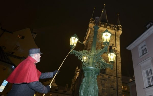 lamplighter on the Charles Bridges lights gas lamp at advent time