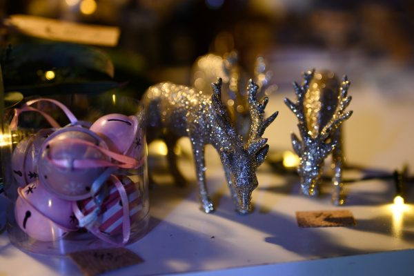 reindeer ornaments next to purple ribbon