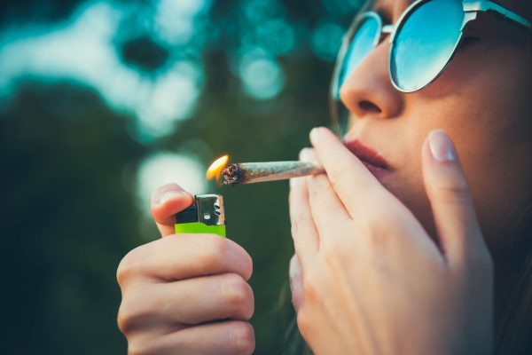 Young woman lighting up a marijuana joint