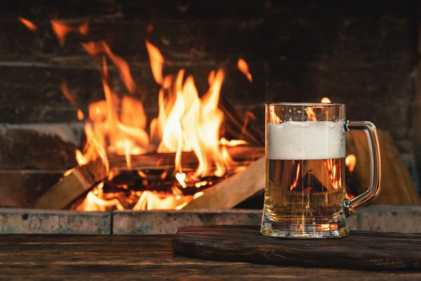 Cold beer by a warm fireplace (illustrative image)