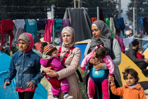 Eidomeni, Greece - March 17, 2016: Two women walk with their children in the refugee camp