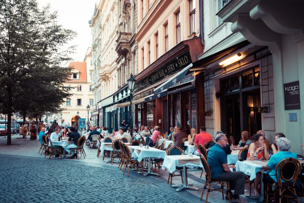 Patrons dining at an outdoor restaurant on Havelská street in Old Town, Prague 1