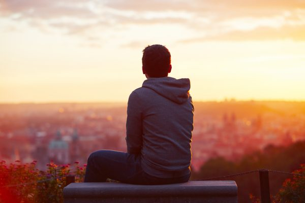 A young man watches the sunrise in Prague via iStock.com / Chalabala