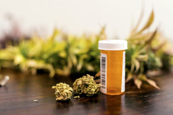 Marijuana buds sitting next to prescription medicine bottle (via iStock / FatCamera)