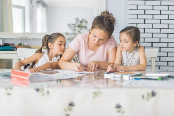 Mother helping daughters with homework