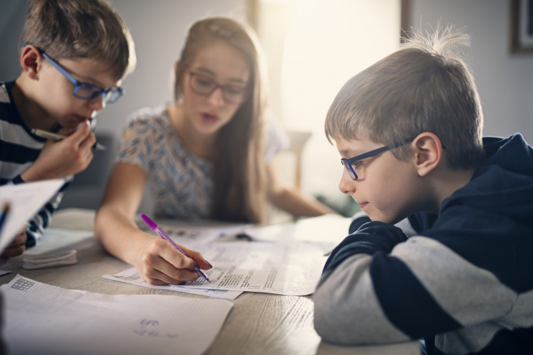 Children doing school work at home via iStock / Imgorthand