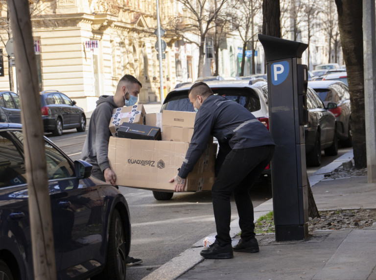Two men wearing face masks carry a box in Prague. Illustrative photo via iStock / Albertem