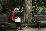 Young woman on a park bench in Prague filling out paperwork before taking a COVID-19 test via iStock / Albertem