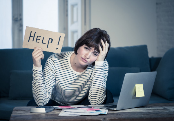 ortrait of worried young woman feeling stressed and desperate asking for help in paying bills, debts, tax expenses and accounting home finances with laptop. In online banking and financial problems. stock photo