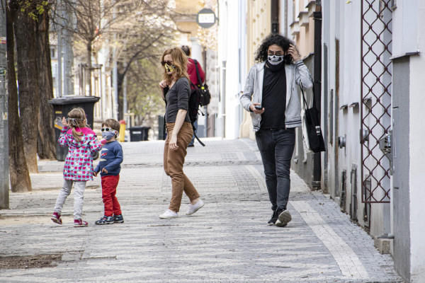Children and adults wearing face masks on the streets of Prague