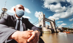 Businessman wearing a face mask by London's Tower Bridge via iStock / franckreporter