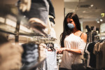 Young woman with face mask in department store via iStock / franckreporter