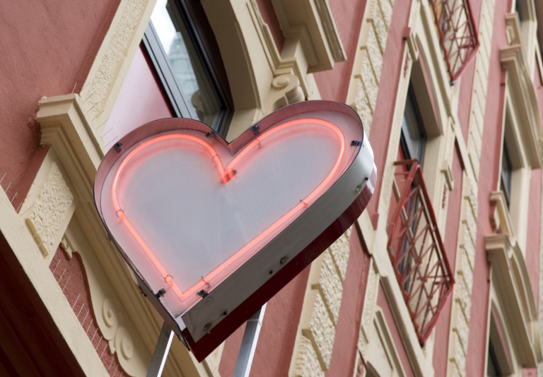 pink neon heart above building