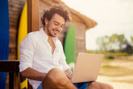 Man using a laptop at a beach bar via iStock / filadendron