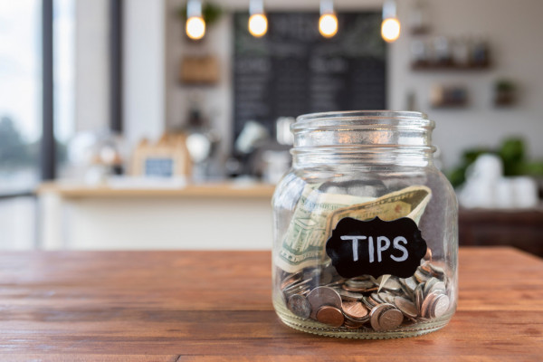 "Foreground focus is on a glass jar labeled ""tips"" in chalk. The jar is sitting to one side on a rustic wooden table, full of coins and bills, with coffee shop scenery in the background."