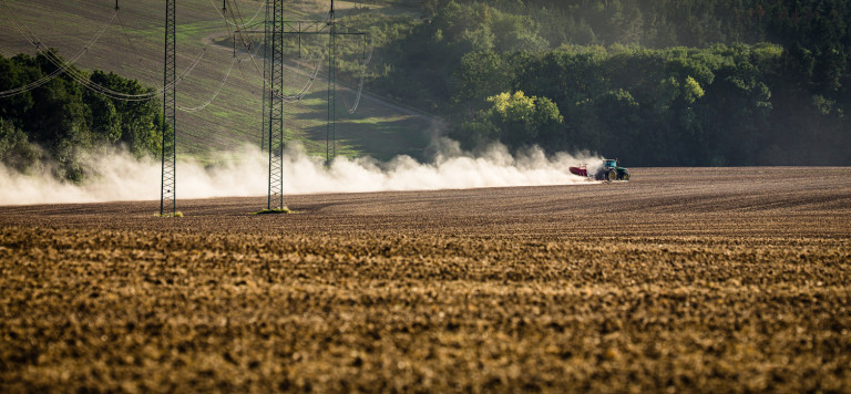 Tractor plowing a dry farm field in rural Czech Republic via iStock / ViktorCap