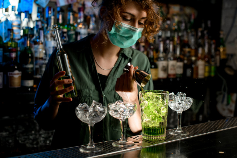 A bartender wearing a face mask pours a mixed drink. Illustrative photo via iStock / MaximFesenko