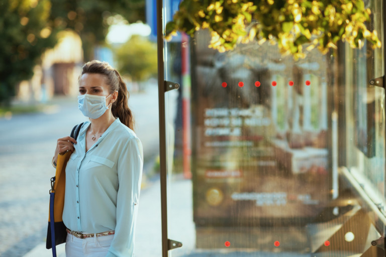 Woman wearing a face mask waits at a Prague bus stop via iStock / CentralITAlliance