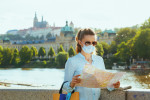 Tourist in Prague wearing a face mask via iStock / CentralITAlliance