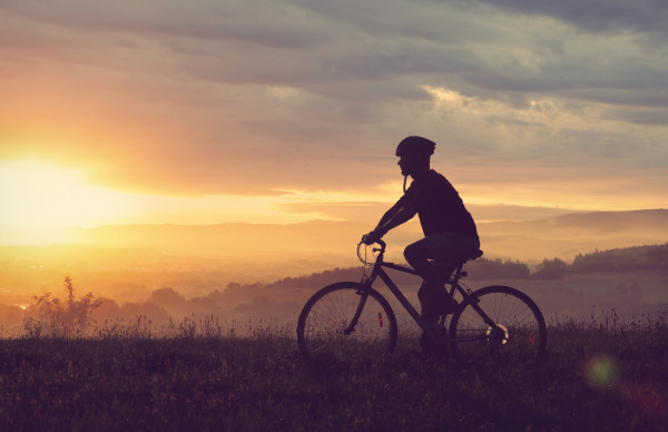 Cyclist going on bicycle in countryside in sunset light