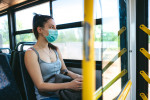 Young woman wearing a face mask on a bus via iStock / urbazon